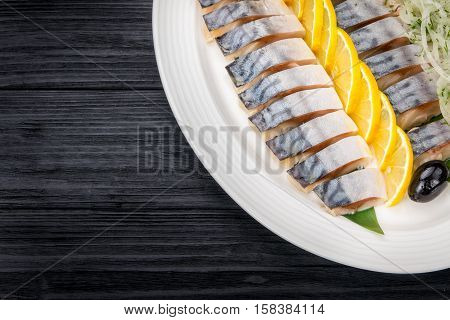 Herring fillets with onion and lemon slices  on old rustic table