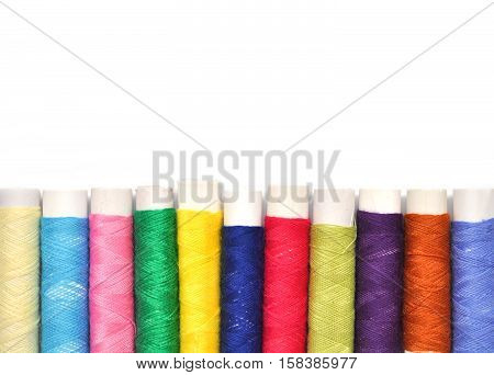 Pile of coloured bobbins of lurex thread isolated on white