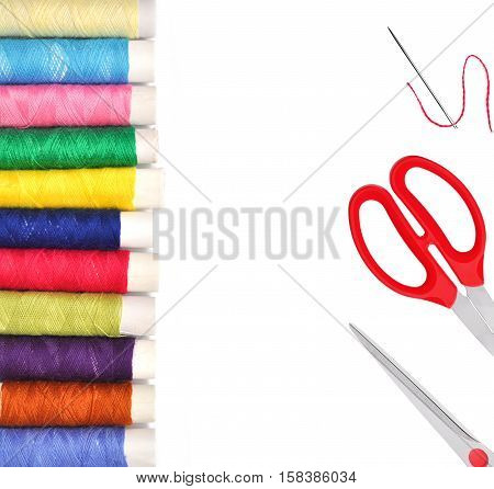 Pile of coloured bobbins of lurex thread and red scissors isolated on white