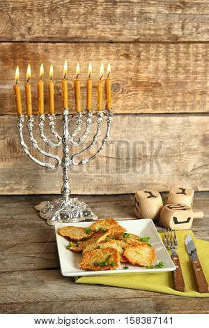 Beautiful composition for Hanukkah on table against wooden background