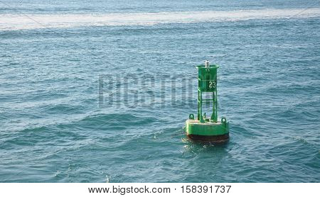 A green ocean buoy that marks a deep passage for boats.