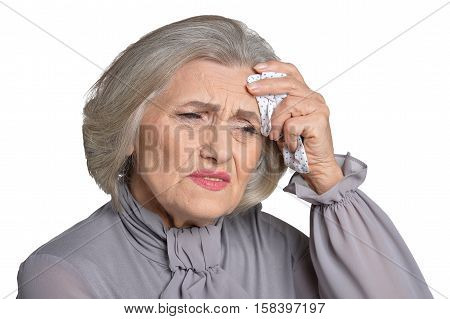 Portrait of sick senior woman in grey blouse with handkerchief  isolated on white background