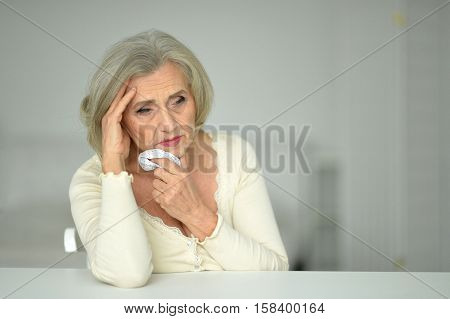 Portrait of senior woman sits at the table and feels sick holding handkerchief