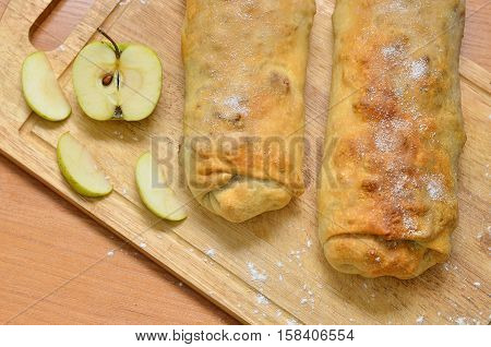 homemade cake - roll strudel. Lying on a wooden cutting board lightly sprinkled with flour. Nearby lies an apple. Space for text Christmas food. A festive meal