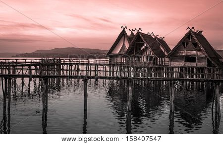 Thatched cottages suspended on stilts over lake - Landscape at sunset with clay houses with thatched roofs suspended on wooden pillar over a lake