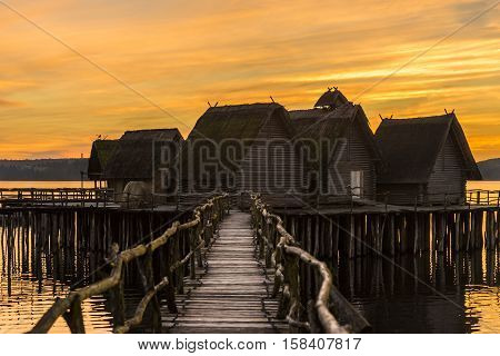 Wooden bridge and houses suspended over lake water - Fishing cabins suspended on wooden pillars over lake's water under a beautiful yellow sky at sunset