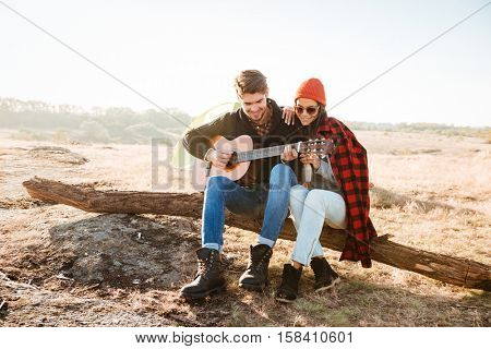 Young pretty couple having fun outdoors with guitar while sitting at the campsite