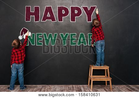 Back view of two little boy twins making happy new year sign with chalks on the blackboard