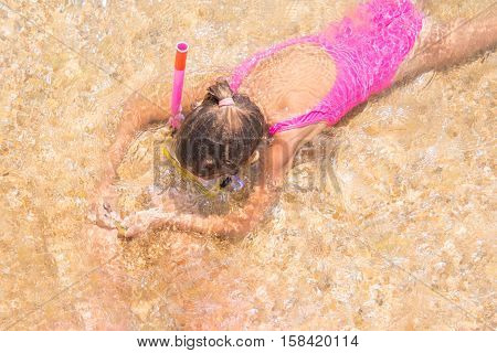 Girl In The Mask And Tube Swims Under Water In Shallow Water