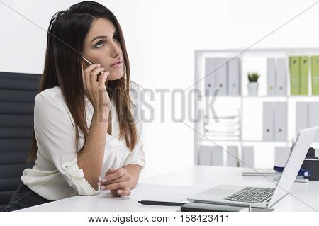 Woman With Long Brown Hair Is On The Phone In A White Office