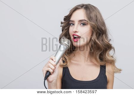 Close up of a singing woman with a large microphone is looking at the camera. She is wearing a black dress. Gray background.