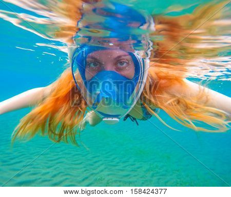 Snorkeling woman with bright red hair. Snorkel in full face mask. Female swimmer mermaid.