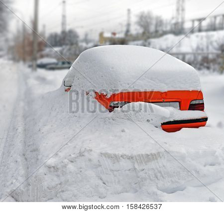 Bright red car in a snowdrift skidded by snow on the parking after a heavy snowfall