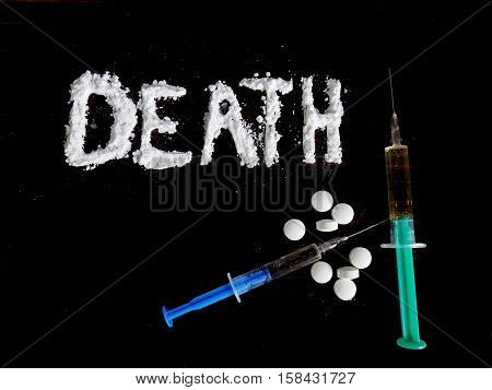 Cocaine drug powder in death word shaped, pills and injections syringe on black background