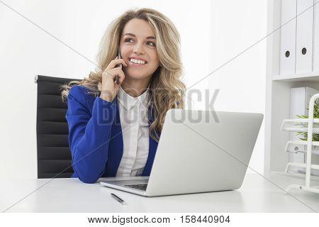 Cherful businesswoman in blue blazer is talking on her cell phone and looking upwards while checking details in her laptop