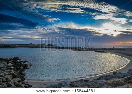 Sunset on beach, transparent waters and clouds over sky