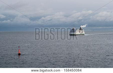 Helsingbog, Sweden - October 9, 2016: The passenger ferry on the line Helsingborg, Sweden - Helsingor, Denmark. In the foreground is seen the sea buoy.