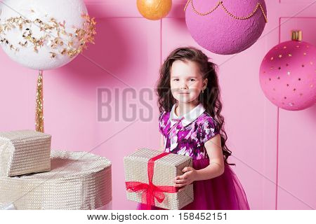 Brunette girl child 5 years old in a pink dress. in holiday rose quartz room with gifts