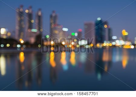 Blurred bokeh lights city office building with reflection night view