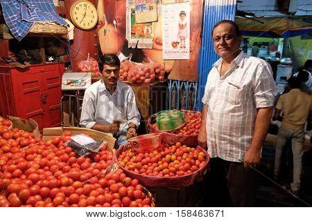 KOLKATA, INDIA - FEBRUARY 11: Indian vendor sits behind a large pile of tomatoes  in New Market in Kolkata on February 11, 2016.