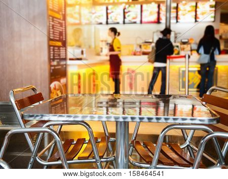 Chinese fast food cafe with metallic table and seats in foregroung and blurred interior in background