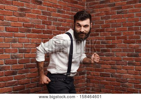 Young handsome man in suit with suspenders smiling dancing posing over brick background. Copy space.