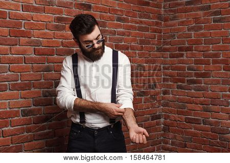 Young handsome man in suit with suspenders correcting shirt over brick background. Copy space.