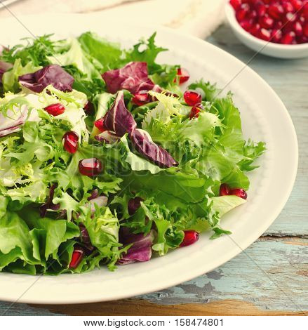 Green salad with spinach, frisee, arugula, radicchio and pomegranate seeds on blue wooden background, toned
