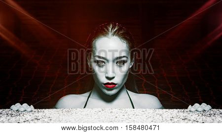 Closeup face of sexy sensual Asian woman with gray eyes,  red lips and wet hair standing in the swimming pool and looking into the camera during summer evening over red lights reflections background