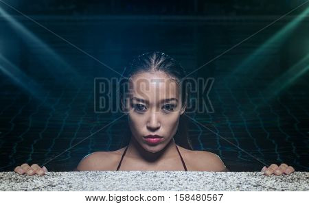 Closeup face of sexy sensual Asian woman with wet hair standing in the swimming pool and looking into the camera during summer evening over blue and green lights reflections background