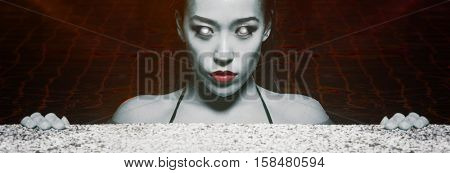 Closeup face of sexy sensual Asian woman with white eyes,  red lips and wet hair standing in the swimming pool and looking into the camera during summer evening over red lights reflections background