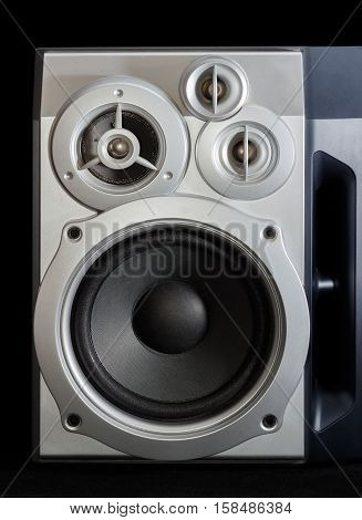 Fragment of home high fidelity three-way loudspeaker system with bass reflex port in silvery housing on a dark background