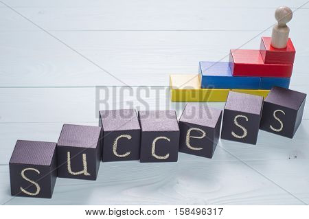 The word success written on a black wooden cubes. Abstract wooden man stands on the top of the ladder made from colorful wooden blocks. The concept of success victories and achievements.