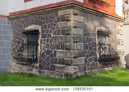 Window with iron grating and old wall of a castle
