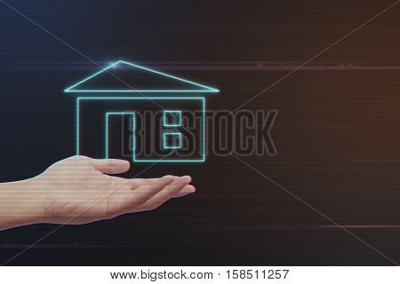 Human Hand Holding Home Icon on Light Motion Background and Lens Flare - Digital 3d Effect Style Color