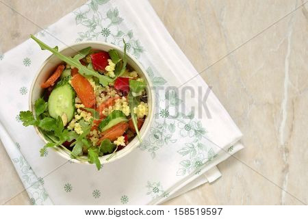 Moroccan salad: carrots millet herbs pepper, top view, copy space