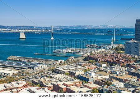 Aerial cityscape of San Francisco Embarcadero and Oakland Bridge from top of Coit Tower on sunny day on Telegraph Hill, California, United States.