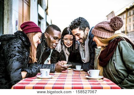 Group of multi-ethnic friends sitting in a bar and talking - Young people having fun outdoors