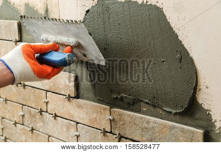 Installing the tiles on the wall. A worker setting tiles in the form of brick. He put adhesive using a trowel.