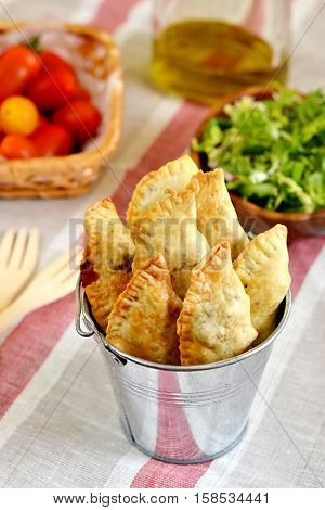 Baked homemade empanadas with tomatoes and lettuce