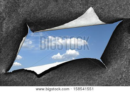 Hole torn in a piece of black rough paper and view of sunny blue sky in it. The concept of motivation liberation from depression hope joy of life the desire for spirituality