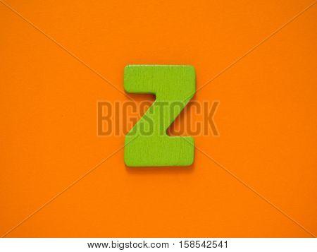 Capital letter Z. Green letter Z from wood on orange background.