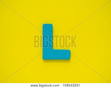 Capital letter L. Blue letter L from wood on Yellow background.