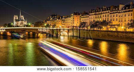 Notre Dame de Paris cathedral illuminated with Seine River and the Tournelle Bridge. Ile Saint Louis, Quai d'Orleans, 4th Arrondissement, Paris, France