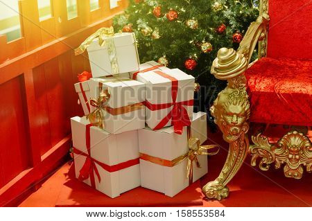 Elegant Christmas gifts presents boxes wraped with red ribbon near luxurious red chair Santa Claus throne surrounded by multiple gift boxes