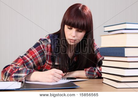 Young Student Girl Doing Homework Writing In Book