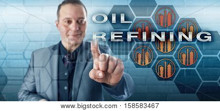 Cheerful hard-edged industrialist with toothless smile is pressing OIL REFINING onscreen. Industrial process and crude oil technology metaphor for the downstream side of the petroleum industry.
