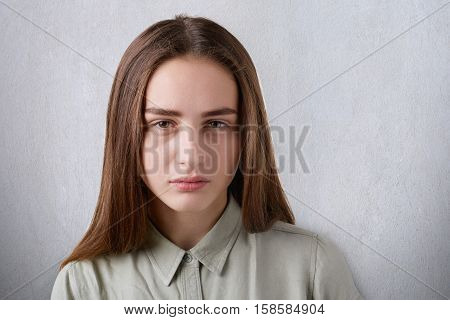 A close-up of a beautiful young girl with shining eyes and straight long dark hair having a sombre face looking straight in the camera. A portrait of cute girl on white background falling to thinking