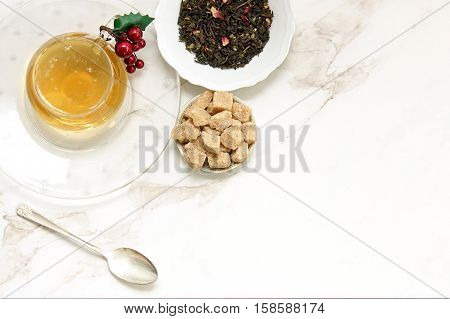 Over head flat lay view of golden herbal tea, loose tea leaves, raw sugar cubes and vintage spoon. Open space for copy.