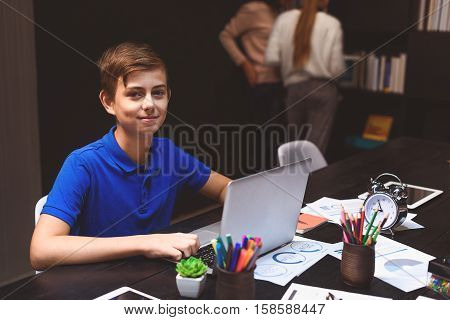 Boy is sitting at table in library and looking at camera with interest while typing on laptop